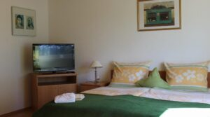 Doppelbett und TV im Zimmer 9 der Pension Witten Höhen in Cuxhaven